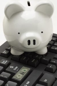 Piggybank conducting electronic banking transaction on computer keyboard